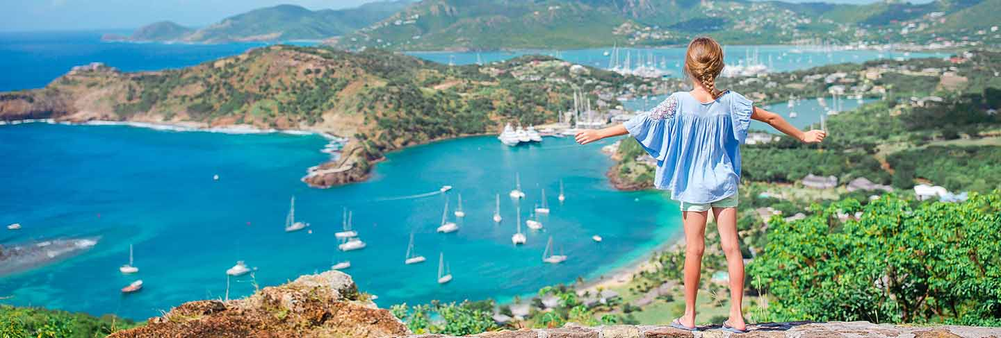 Adorable little kid enjoying the view of picturesque english harbour at antigua in caribbean