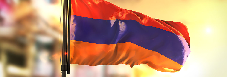 Armenia flag against city blurred background at sunrise backlight