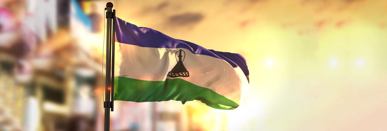 Lesotho flag against city blurred background at sunrise