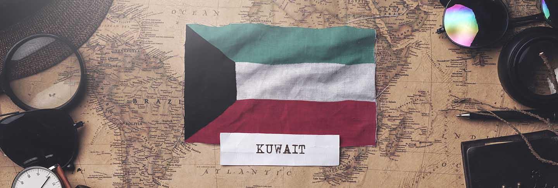 Kuwait flag between traveler's accessories on old vintage map
