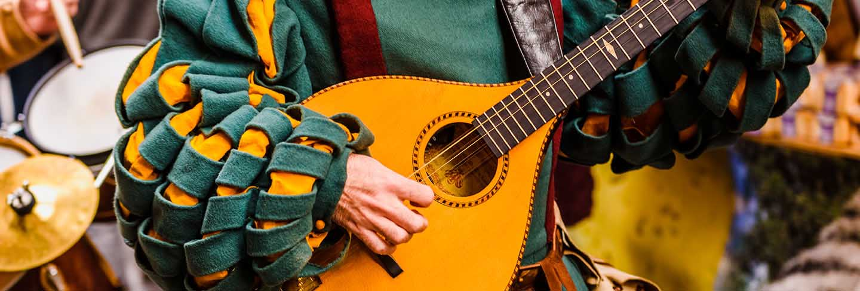 Medieval troubadour playing an antique guitar.