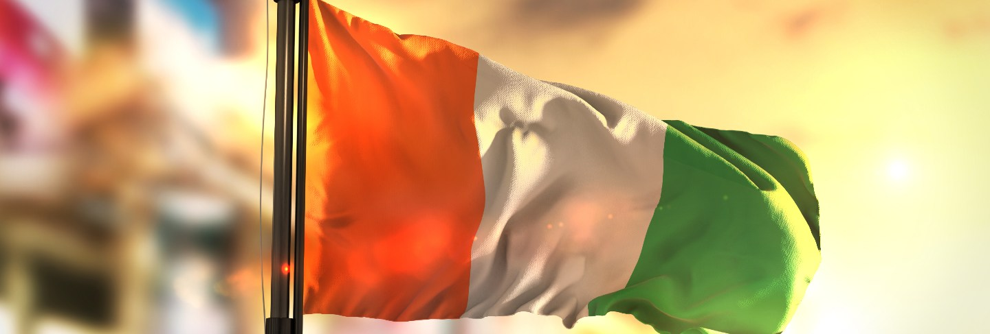Ivory coast flag against city blurred background at sunrise backlight