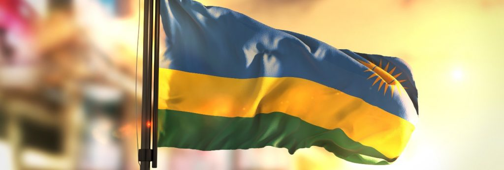 Rwanda flag against city blurred background at sunrise backlight