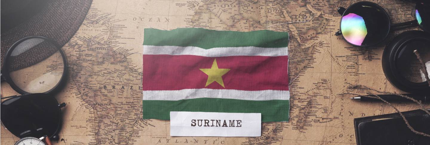 Suriname flag between traveler's accessories on old vintage map