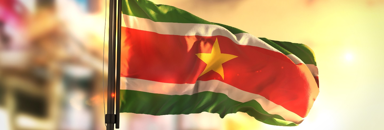Suriname flag against city blurred background at sunrise backlight
