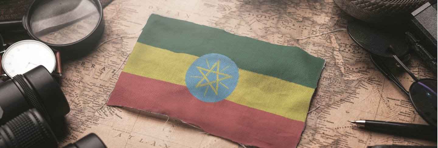 Ethiopia flag between traveler's accessories on old vintage map. tourist destination concept.