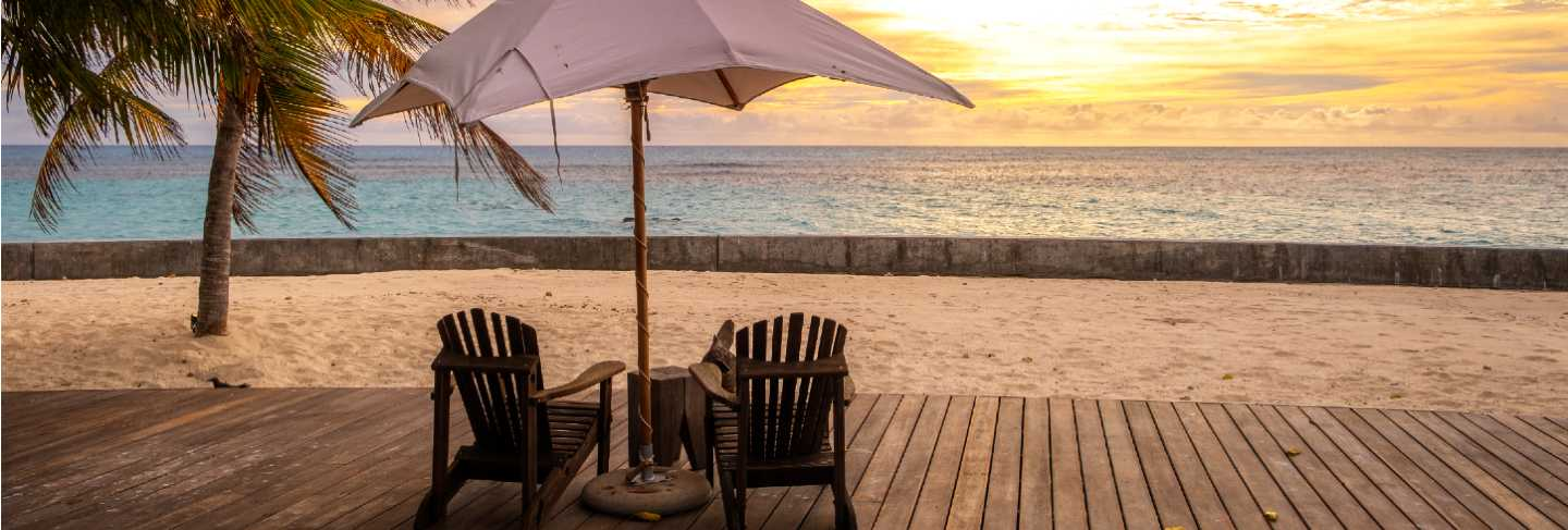 Umbrella and deck chairs on the beautiful tropical beach and sea at sunset time for travel and vacation