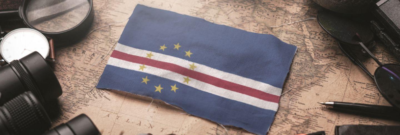 Cape verde flag between traveler's accessories on old vintage map. tourist destination concept.