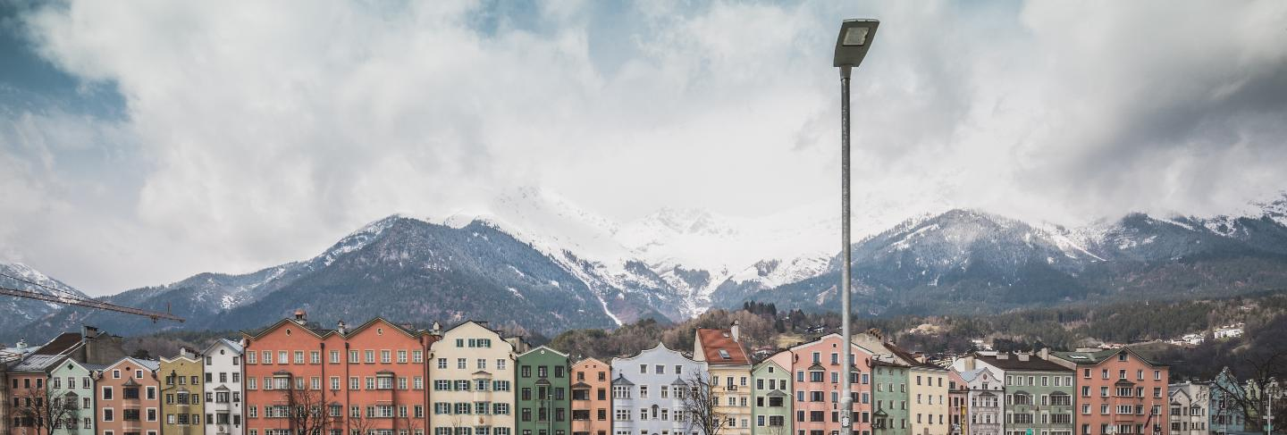 View of the historic city center of innsbruck with colorful houses along inn river and famous austrian mountain summits in the background with a bike, tyrol, austria