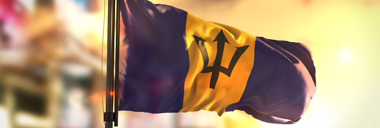 Barbados flag against city blurred background at sunrise backlight
