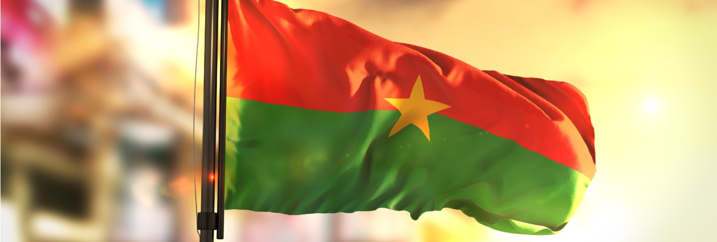 Burkina faso flag against city blurred background at sunrise backlight