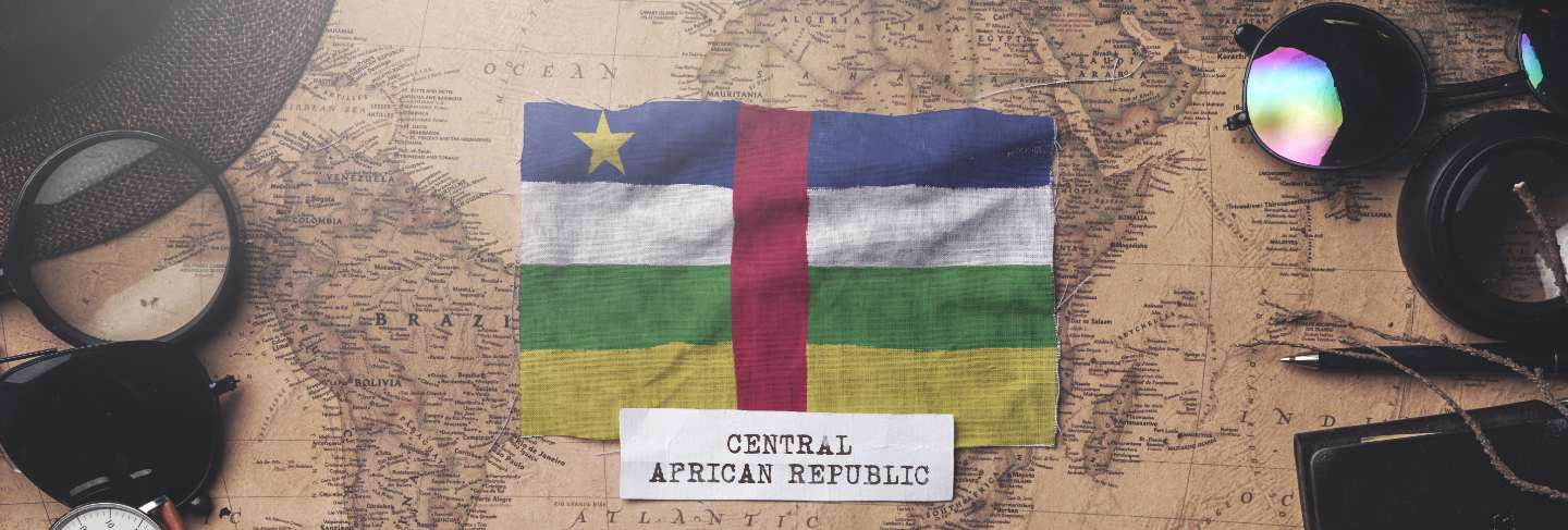 Central african republic flag between traveler's accessories on old vintage map. overhead shot