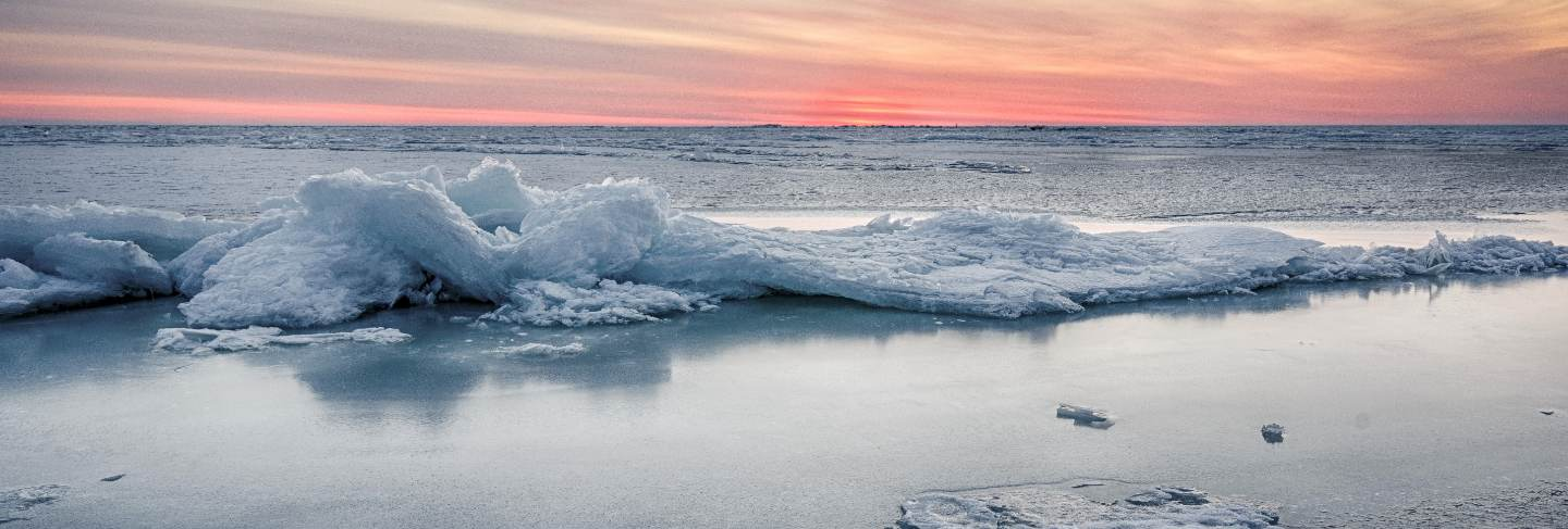 Abstract frozen winter sunrise seascape with ice and colored the sky