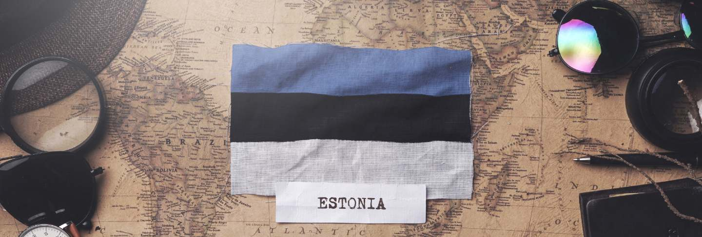 Estonia flag between traveler's accessories on old vintage map. overhead shot