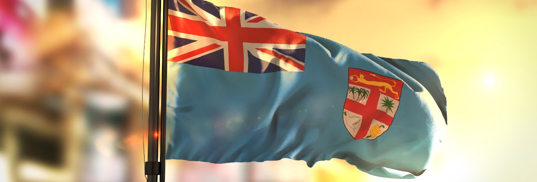 Fiji flag against city blurred background at sunrise backlight