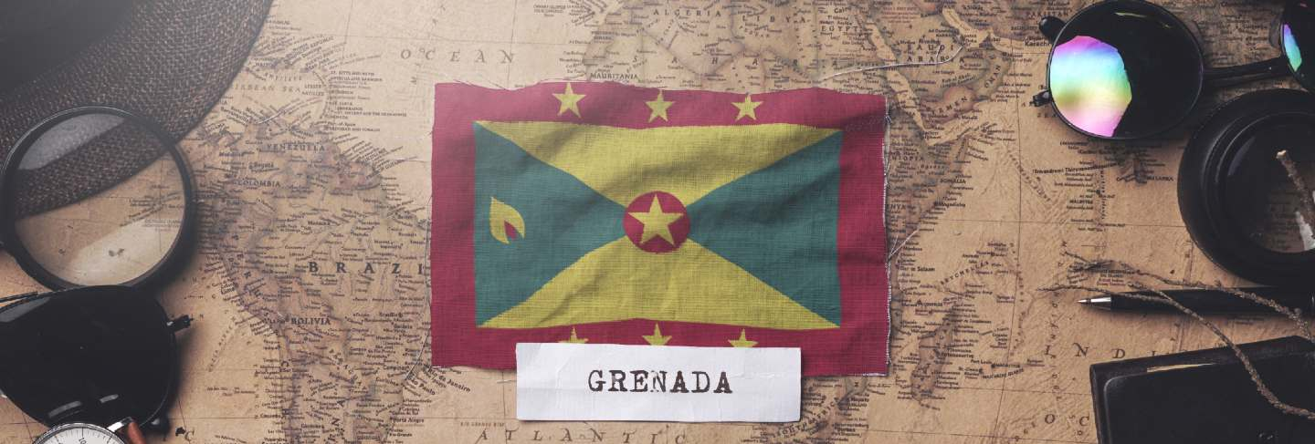 Grenada flag between traveler's accessories on old vintage map. overhead shot
