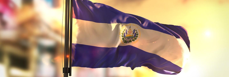 El salvador flag against city blurred background at sunrise backlight