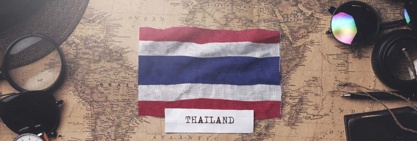 Thailand flag between traveler's accessories on old vintage map