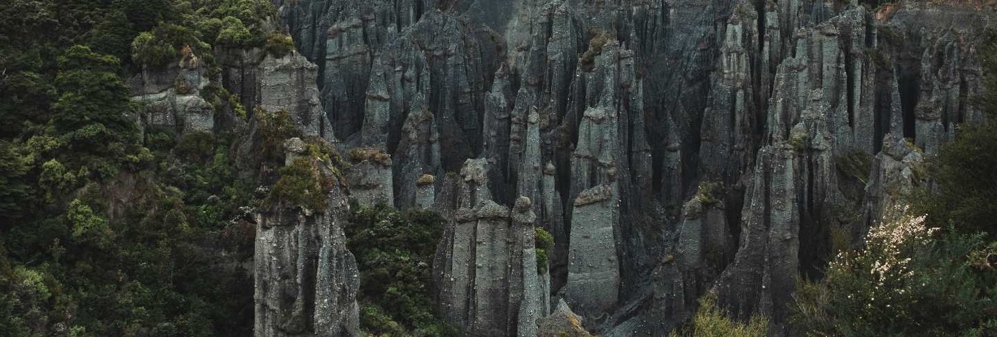 Beautiful aerial shot of rocks formation between forest on a hill
