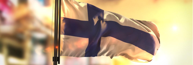 Finland flag against city blurred background at sunrise backlight