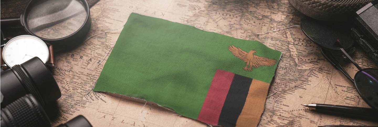 Zambia flag between traveler's accessories on old vintage map. tourist destination concept