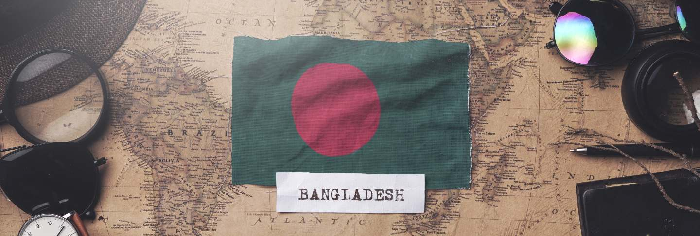 Bangladesh flag between traveler's accessories on old vintage map.