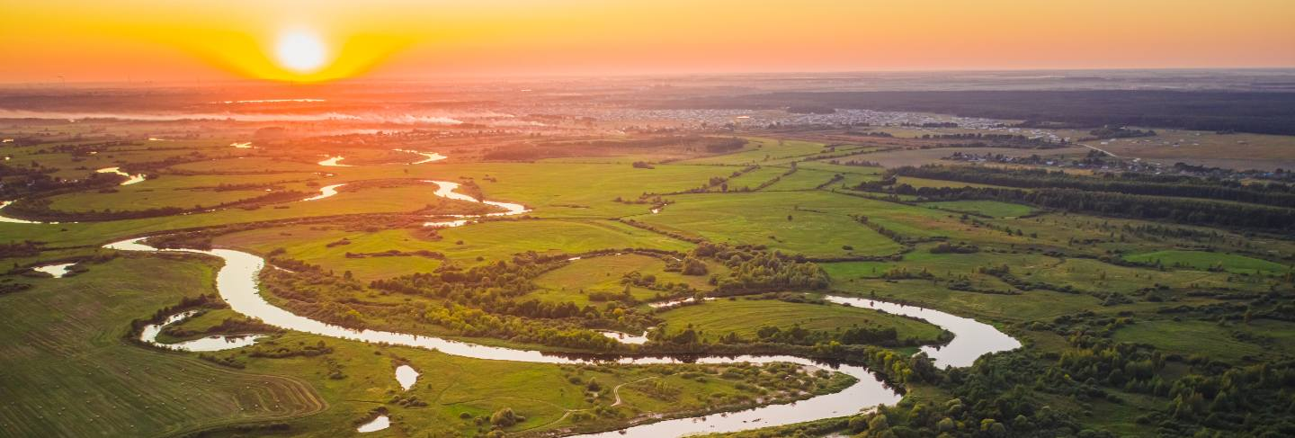Beautiful summer sunset over a river with forests and fields