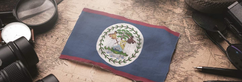 Belize flag between traveler's accessories on old vintage map. tourist destination concept.