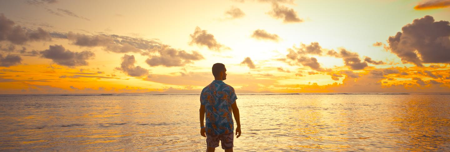 Tropical sunset in front of the ocean on a beautiful island. man on vacation enjoying the moment