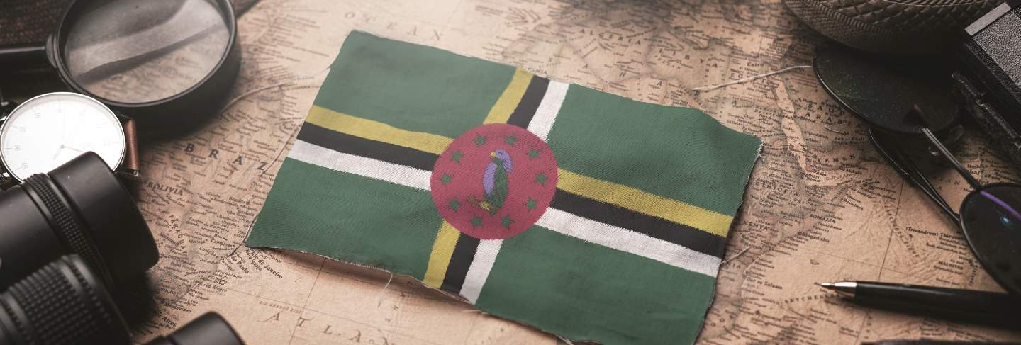 Dominica flag between traveler's accessories on old vintage map. tourist destination concept