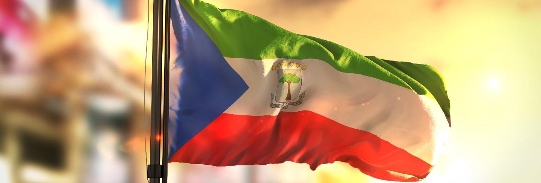 Equatorial guinea flag against city blurred background at sunrise backlight