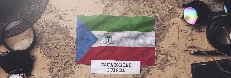 Equatorial guinea flag between traveler's accessories on old vintage map. overhead shot