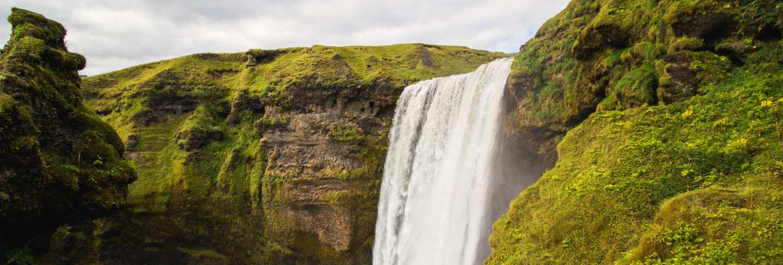 Waterfall between green mountains