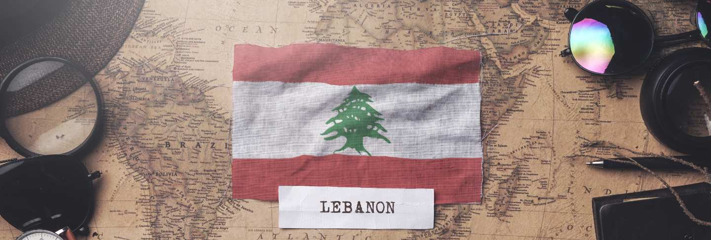 Lebanon flag between traveler's accessories on old vintage map. overhead shot