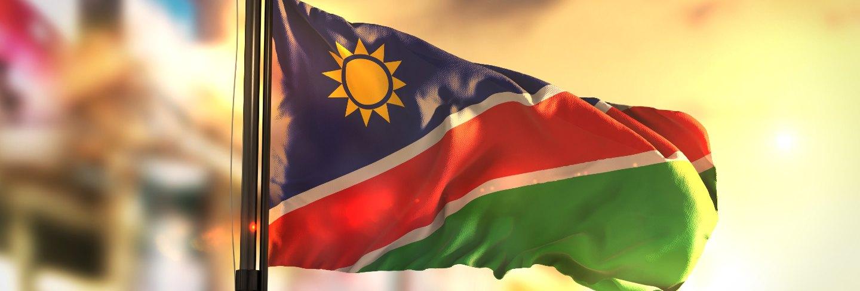 namibia-flag-against-city-blurred-background-sunrise-backlight