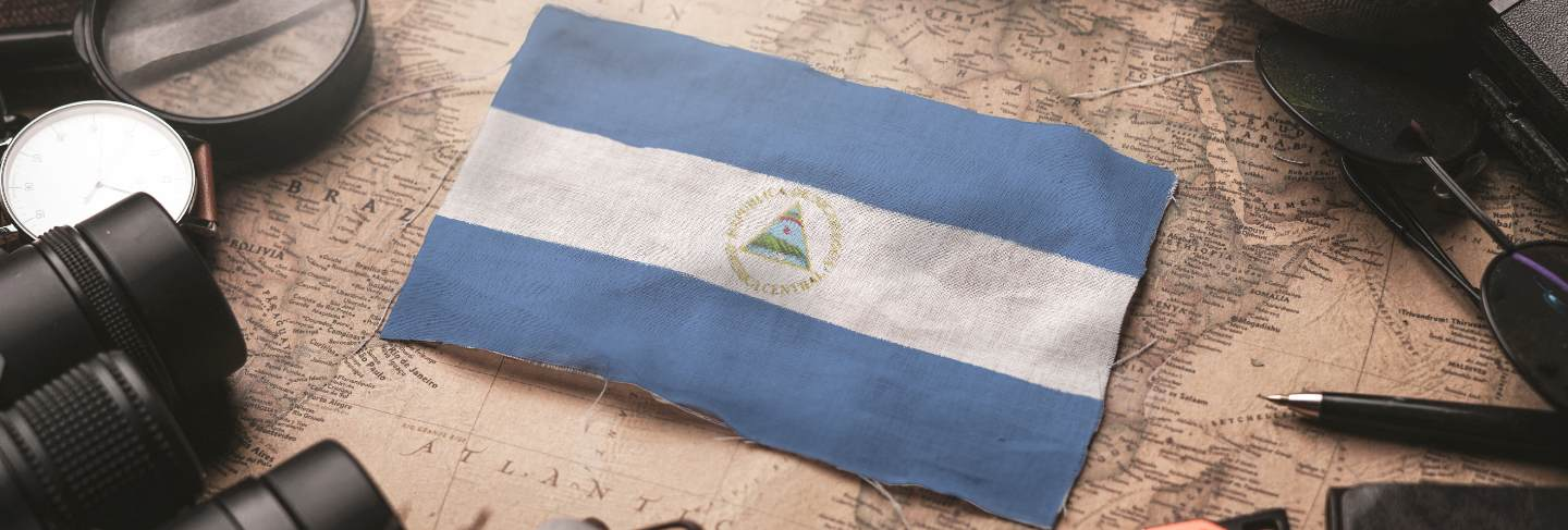 Nicaragua flag between traveler's accessories on old vintage map. tourist destination concept