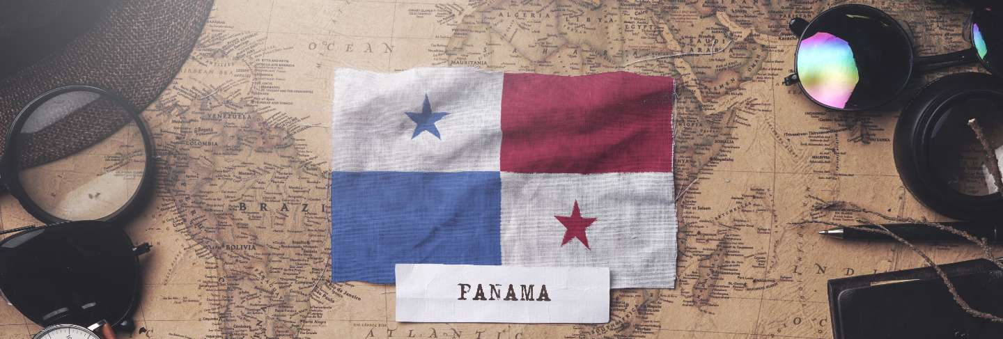 Panama flag between traveler's accessories on old vintage map. overhead shot