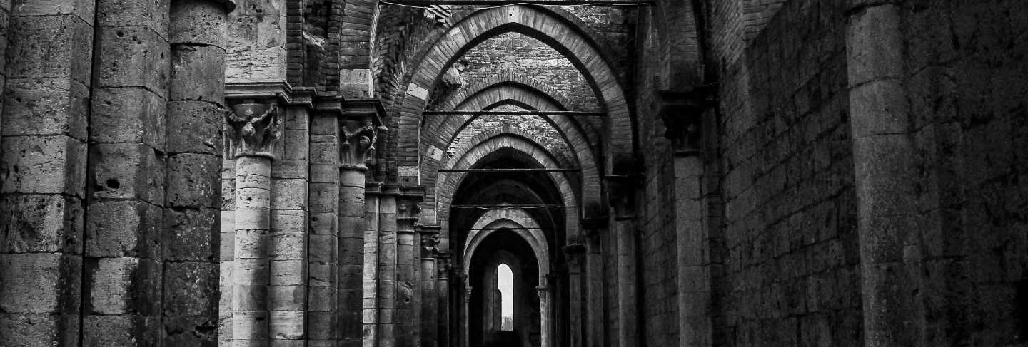 Vertical shot of a hallway with pillars and arched type doorways at abbazia di san galgano