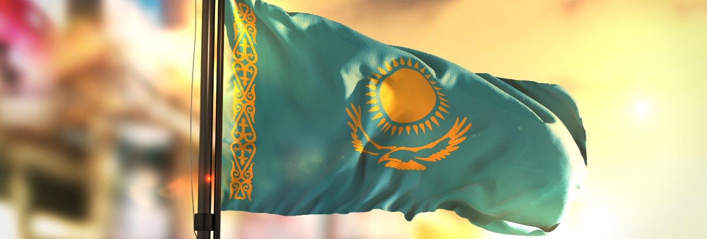 Kazakhstan flag against city blurred background at sunrise backlight