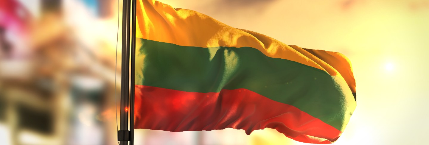 Lithuania flag against city blurred background at sunrise backlight