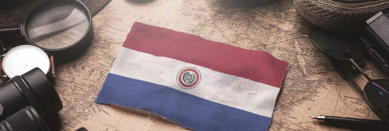 Paraguay flag between traveler's accessories on old vintage map. tourist destination concept.