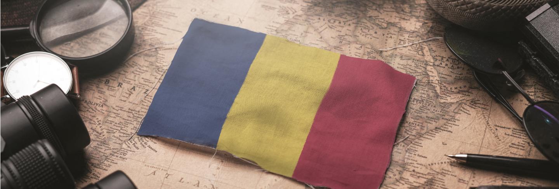 Romania flag between traveler's accessories on old vintage map. tourist destination concept.