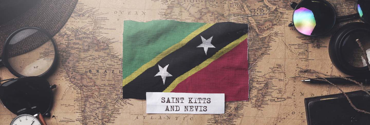 Saint kitts and nevis flag between traveler's accessories on old vintage map.