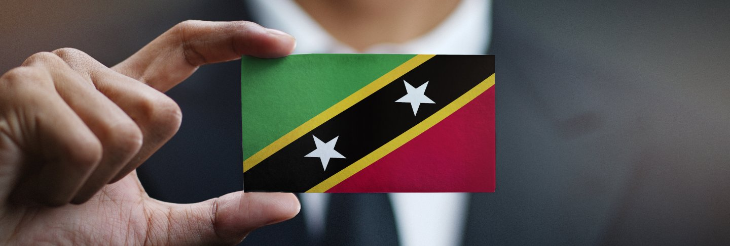 Businessman holding card of saint kitts and nevis flag