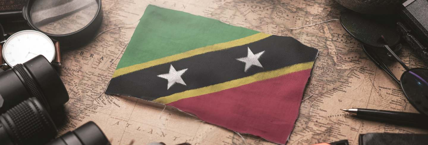 Saint kitts and nevis flag between traveler's accessories on old vintage map. tourist destination concept.