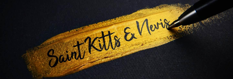 Saint kitts and nevis handwriting text on golden paint brush stroke