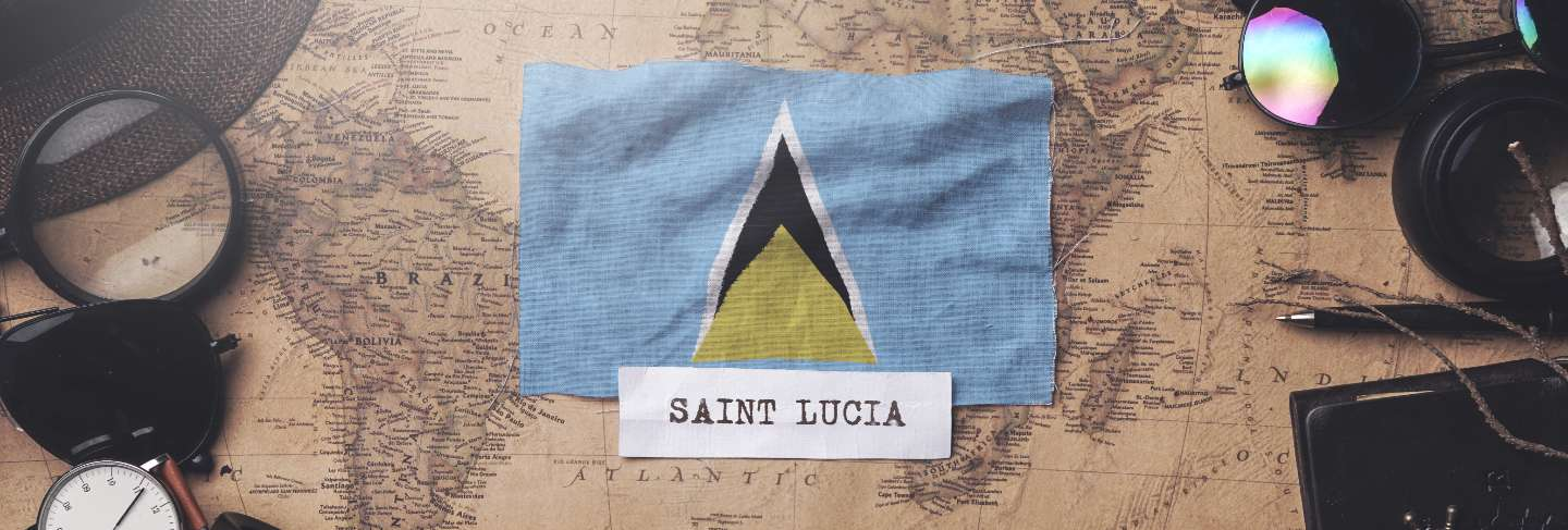 Saint lucia flag between traveler's accessories on old vintage map.