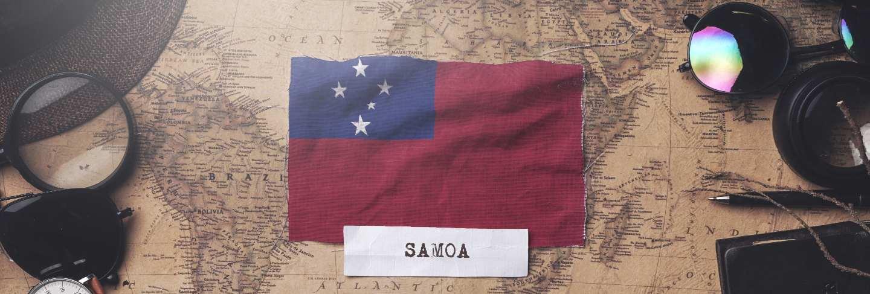 Samoa flag between traveler's accessories on old vintage map.