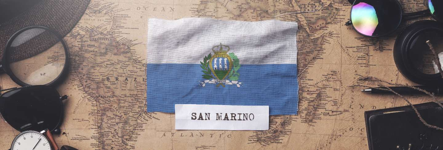 San marino flag between traveler's accessories on old vintage map.