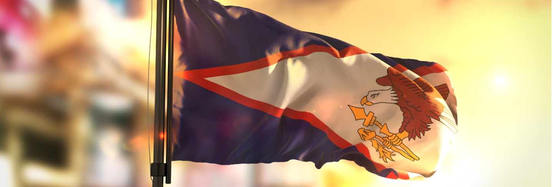 American samoa flag against city blurred background at sunrise backlight